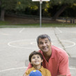 Hispanic father and son on basketball court — Zdjęcie stockowe