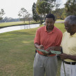 African father and adult son on golf course — Stock Photo