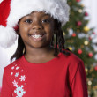 African girl wearing Santa Claus hat — Stock Photo #23317284