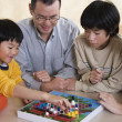 Asian family playing board game — Stock Photo #23317286