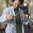 Stock Photo: Mixed Race male hair stylist holding scissors