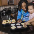 African mother and daughter making cupcakes — Stock Photo