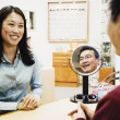 Asian optician assisting customer — Stock Photo
