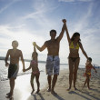 Hispanic family holding hands at beach — Stock Photo