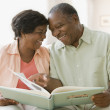 Senior African couple looking at photo album — Stock Photo #23317686