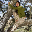 Hispanic woman sitting in tree — Stock Photo #23317730
