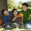 Multi-ethnic family with pumpkins under tree — Stock Photo