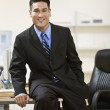 Asian businessman sitting on edge of desk — Foto Stock