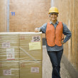 Hispanic warehouse worker next to shipment — Stock Photo
