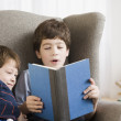 Hispanic boy reading to brother — Lizenzfreies Foto