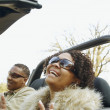 African couple driving in convertible car — Stockfoto