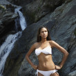 Hispanic woman in bikini next to waterfall — Stock Photo