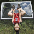 Asian boy hanging upside down on basketball hoop — Stock Photo #23317922