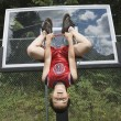Asian boy hanging upside down on basketball hoop — Stock Photo