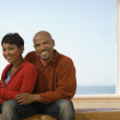 African couple sitting in front of window — Stock Photo