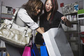Multi-ethnic women looking in shopping bag — Stock Photo