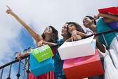 Hispanic friends holding shopping bags — Stock Photo