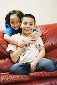 Asian siblings hugging on sofa — Stock Photo