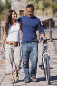 Hispanic couple walking with bicycle — Stock Photo
