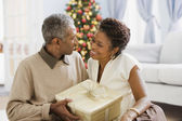 African couple holding Christmas gift — Stock Photo