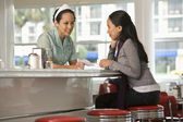 Asian waitress giving bill to customer — Stock Photo