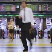 Blurred motion shot of Asian businessman in subway — Stock Photo