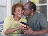 Senior African woman giving gift to husband — Stock Photo