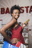African woman holding shopping bag in salon — Stock Photo