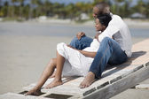 Multi-ethnic couple hugging at beach — Stock Photo