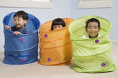 Asian siblings playing in tubes — Stock Photo