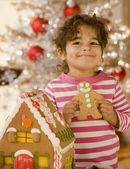 Hispanic girl next to gingerbread house — Stock Photo