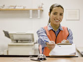 Hispanic businesswoman holding out clipboard — Stock Photo
