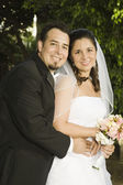 Hispanic bride and groom hugging — Stock Photo