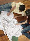Multi-ethnic couple looking at blueprints — Stock Photo