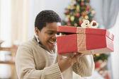 African boy peeking into gift — Stock Photo
