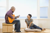 African man playing guitar for wife — Stock Photo