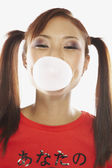 Asian woman blowing bubble with bubble gum — Stock Photo