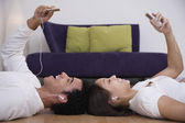 African couple listening to mp3 players — Stock Photo