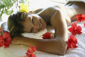 Hispanic woman laying on spa table — Stock Photo