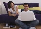 African couple looking at laptop — Stock Photo