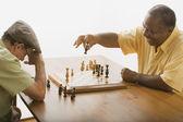 Multi-ethnic senior men playing chess — Stock Photo