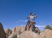 African man with mountain bike on rocks — Stock Photo