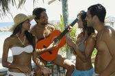 Hispanic man playing guitar for friends — Stock Photo