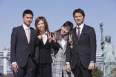 Asian businesspeople standing arm in arm — Stock Photo