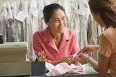 Asian female dry cleaner and customer looking at stain — Foto Stock
