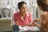 Tintorería mujer asiática y cliente mirando mancha — Foto de Stock