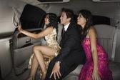 Multi-ethnic friends sitting in limousine — Stock Photo