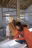 Hispanic architects looking at blueprints — Stock Photo