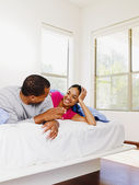 African couple talking in bed — Stock Photo