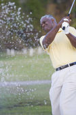 African man swinging golf club — Stock Photo